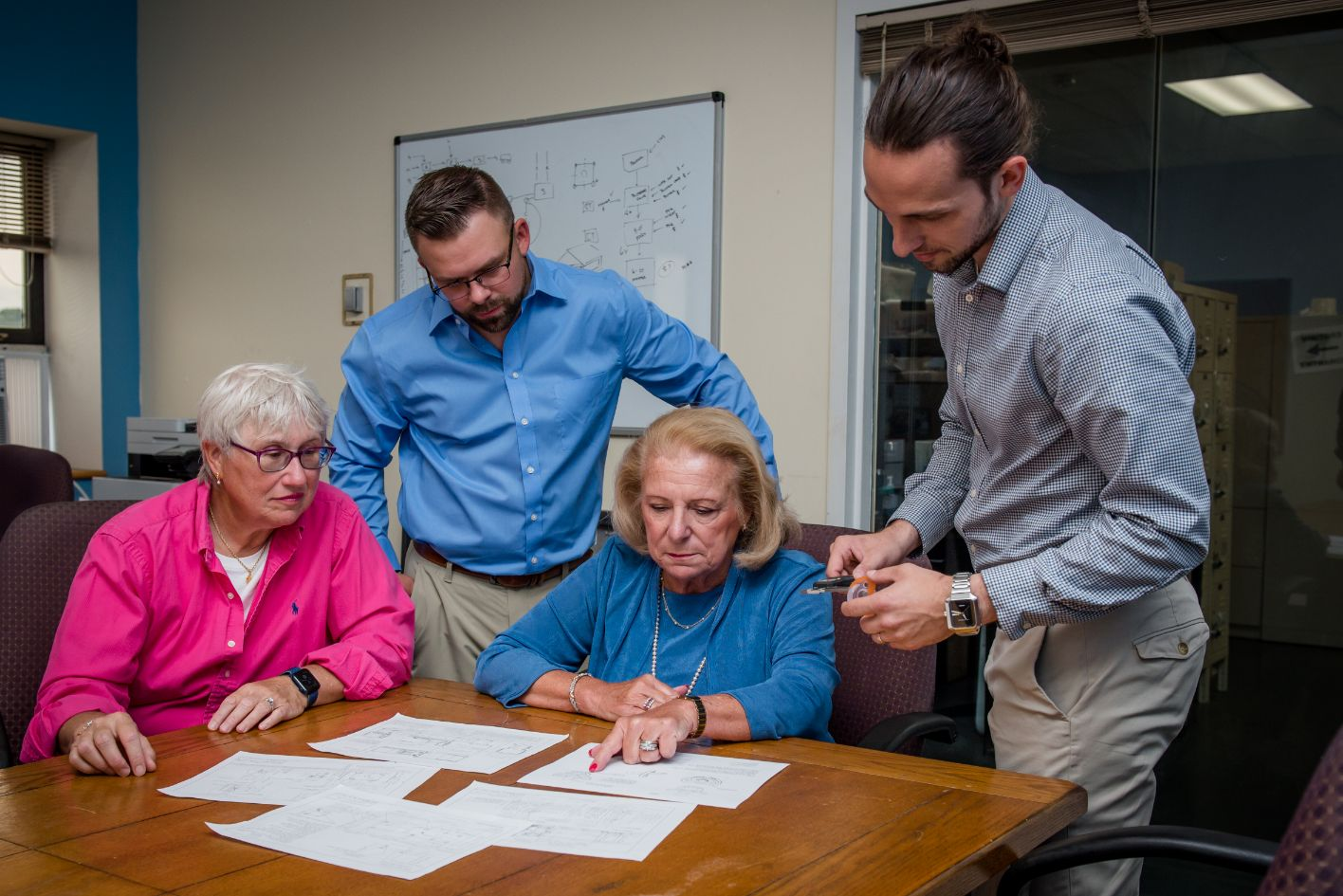 Extreme Molding Approach team members looking at injection molding plans